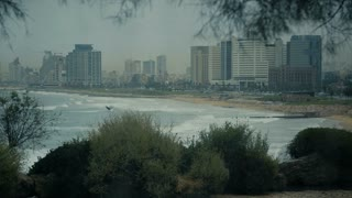 Drops of rain on a window glass. Through the window view of the beach, sea and the resort city in Tel Aviv, Israel, cca 2015.