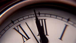 Extreme close-up view of clock at the last 3 seconds to midnight.
