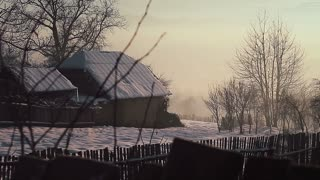 Farm house and barn on early morning winter landscape. Romania, circa 2015.