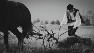 Farmer plowing a field with two horses. Black and white.  Transylvania (central part of Romania) � circa 1940.