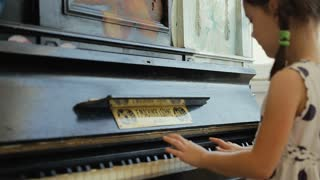 Girl playing the piano in the empty classroom.