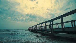 Old wooden jetty after storm on the sea.