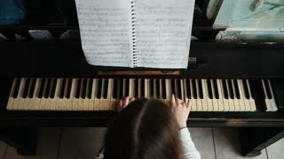 Playing piano music. Girl practicing on classical instrument. Medium shot.