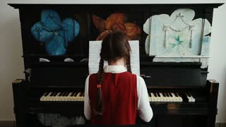 Playing piano music. Girl practicing on classical instrument.