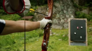 Profile of four archers in a row aiming their bows in an archery contest.