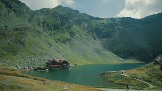 Red wooden house on glacier lake with very clean water in Fagaras Mountains, Romania.