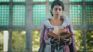 Retro baroque fashion woman wearing violet dress. Hands holding old bible.