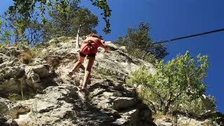 Rock climber securing with carabiner and rope.