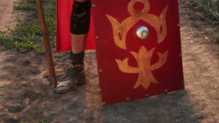 Roman legionary with shield, sword and spear in a cornfield.