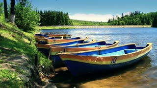 Row Boat moored near shore. Ripple lake water. Boat rental business.