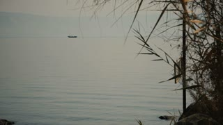 Sea of Galilee in the early morning, ripples on the water and boat. Israel, cca. 2015