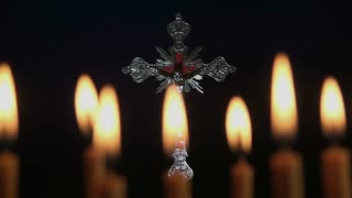 Small silver crucifix near lighting candle.