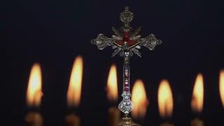Small silver crucifix near lighting candle.