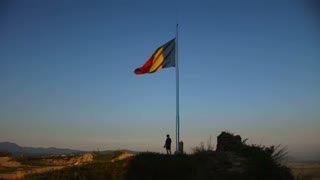 The Romanian flag flies proudly on top of mountain.