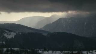 Timelapse of dramatic clouds over mountain peak.