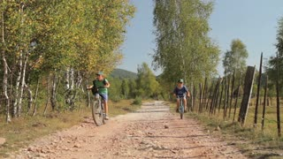 Two young boys on bicycles at the countryside.