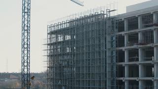 Big crane moving over a high building