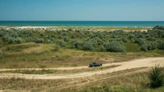 Car driving on a country road with the Black Sea at horizon