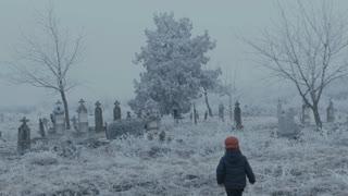 Child walking in a graveyard on winter