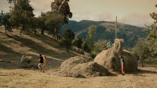Children building a haystack