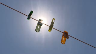 Colorful clips on string with blue sky and bright sun