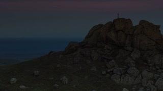 Cross on mountain peak and sunrise - pan shot