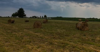 Field with straw bales after rain - time lapse