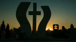 Funeral crosses and cemetery at sunset