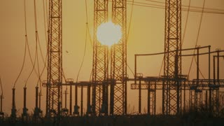 High voltage power lines with the sun on background