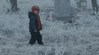 Little child in a graveyard on winter