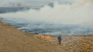 Man burning weeds on agricultural fields in autumn
