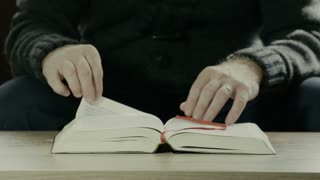 Man turning pages of the Holy Bible