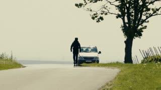 Man walking on the road towards his car - slo mo