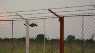 Military Red Cross helicopter through wire fence