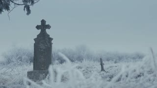 Old stone cross in cemetery on winter