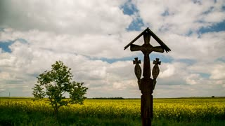 Rape field with wooden cross and dramatic sky. Magic Lantern Raw Video
