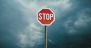 Red stop sign with stormy sky