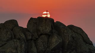 Red sun goes down beyond a hill with cross and rocks