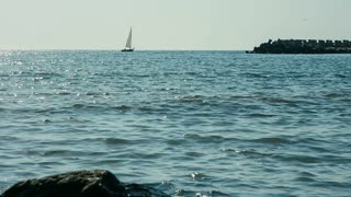 Sea landscape with sailboat and rocky coastline at the Black Sea