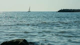 Sea landscape with sailboat and rocky coastline at the Black Sea