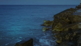 Sea waves and rocks at night - time lapse and motion blur