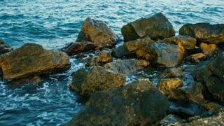 Sea waves crashing on rocks - pan shot