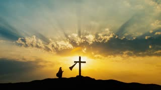 Silhouette of woman praying at Cross over beautiful sky