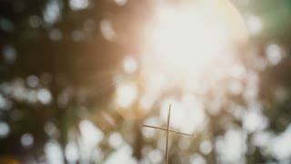 Small christian cross from sticks on a bokeh background