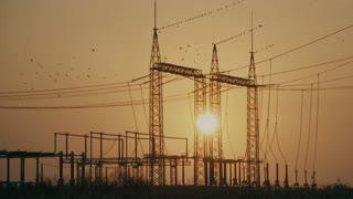 Sun behind high voltage power lines