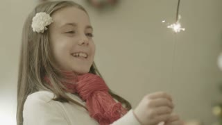 Young girl holding a burning sparkler - joy