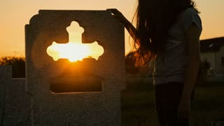 Young lady near a funeral cross at sunset