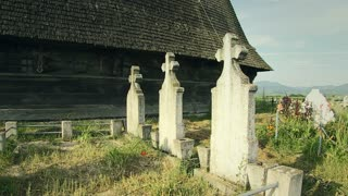 Wooden church surrounded by old cemetery in mountain village, Transylvania, Romania - 2014.