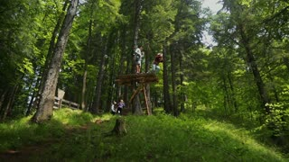 Youth people enjoying zip line in Carpathian Mountains, Romania - 2015. Professional climbing gear with helmet pulley and carabiner.