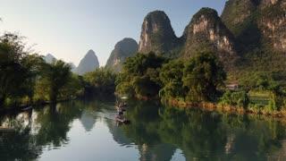People taking bamboo raft along Yulong River, Yangshuo, Guangxi, China